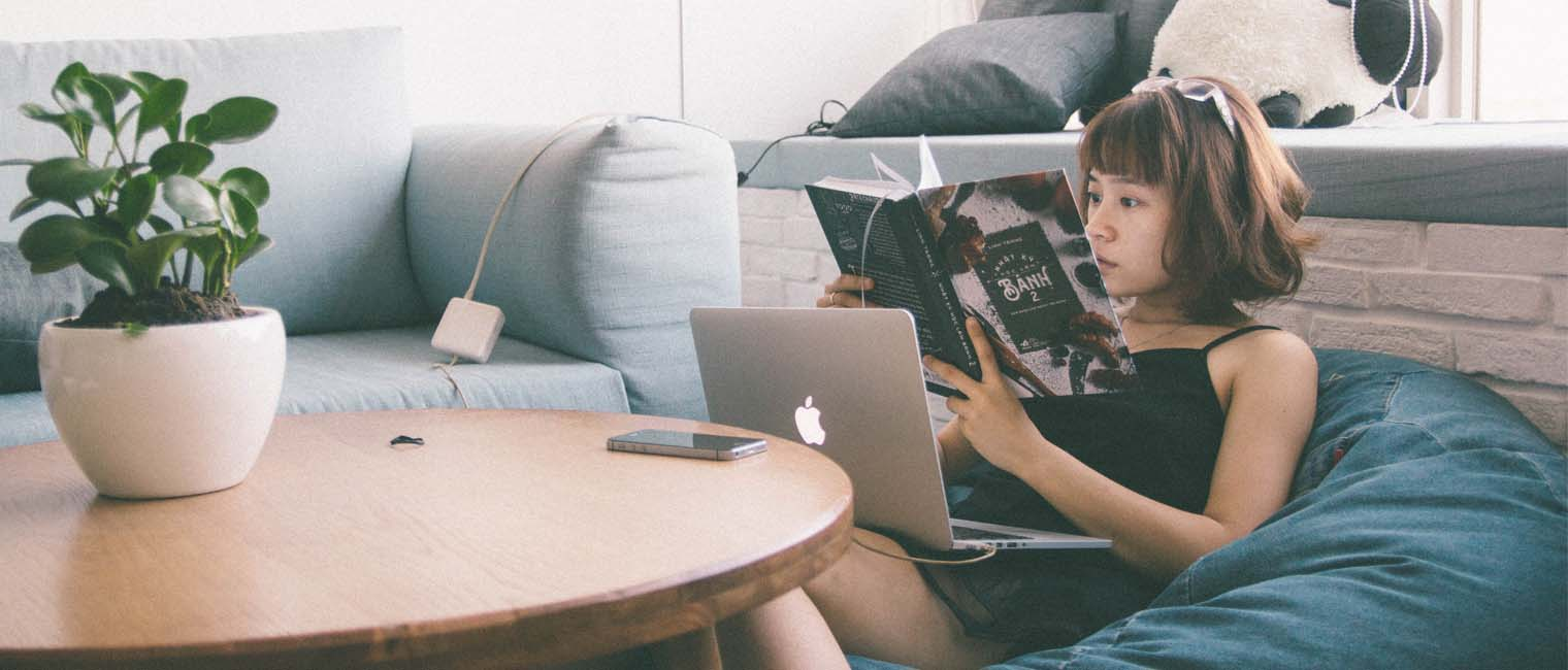 girl sitting in a couch reading a book