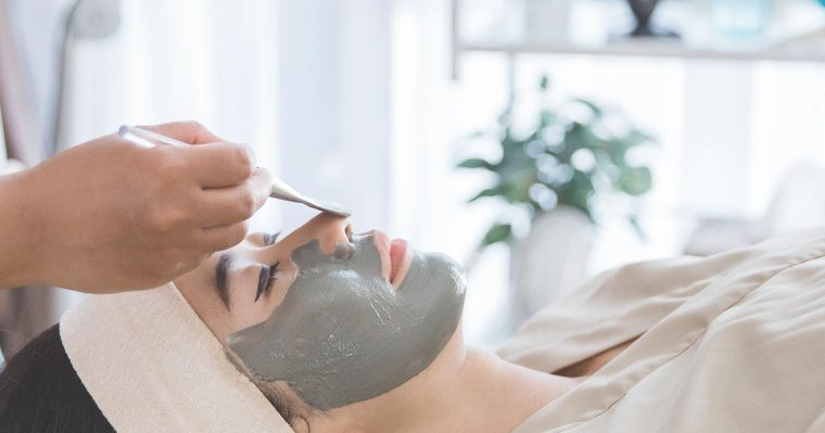 applying clay mask and chemical to a lady's face