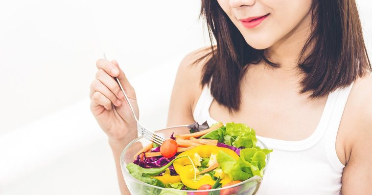 beautiful lady eating a bowl of salad