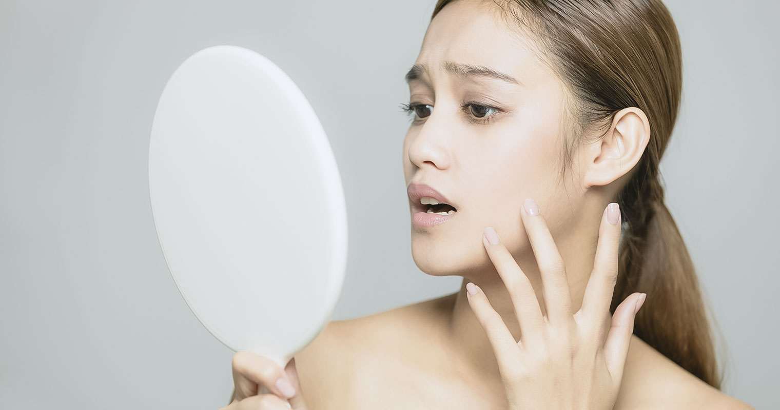 Woman looking into a mirror worried about her skin condition
