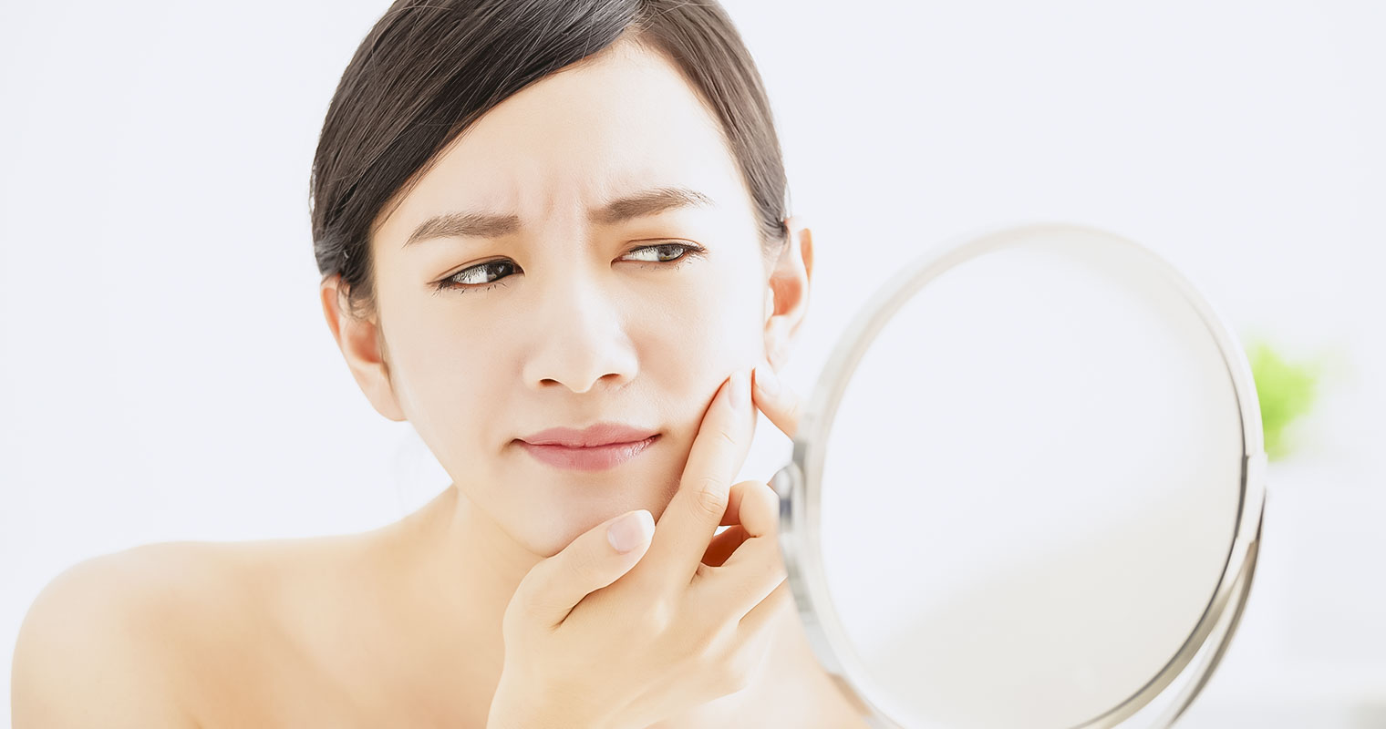 Woman looking into a mirror pricking her pimple