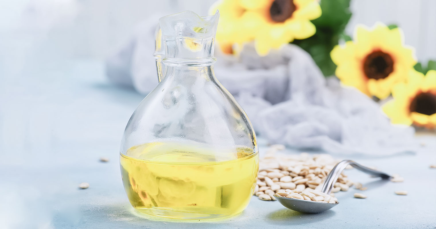 A jar of sunflower oil with sunflower and seeds in the background