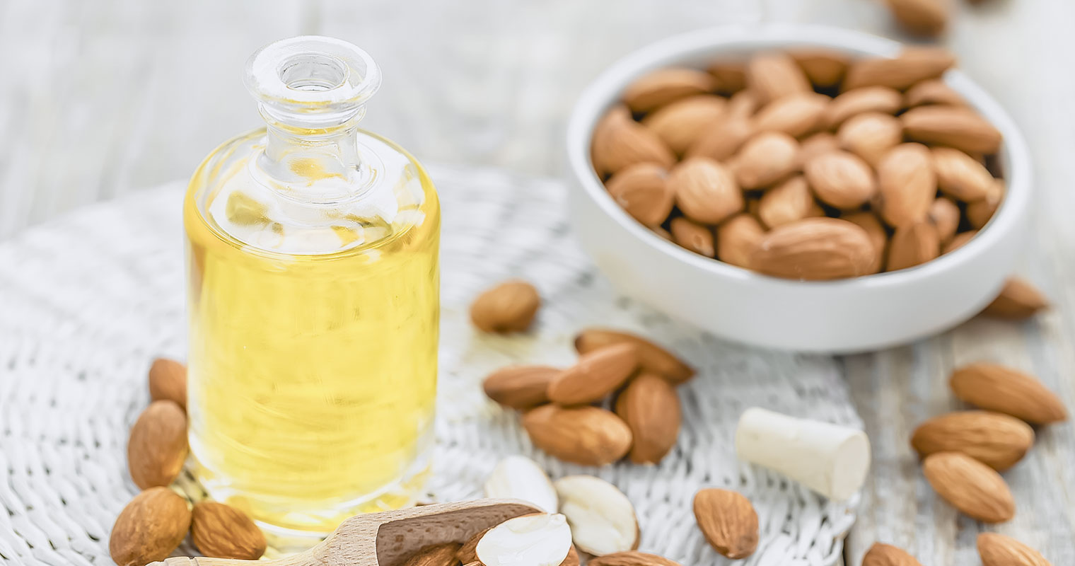 Open bottle of Almond oil and a dish with Almond seeds in the background
