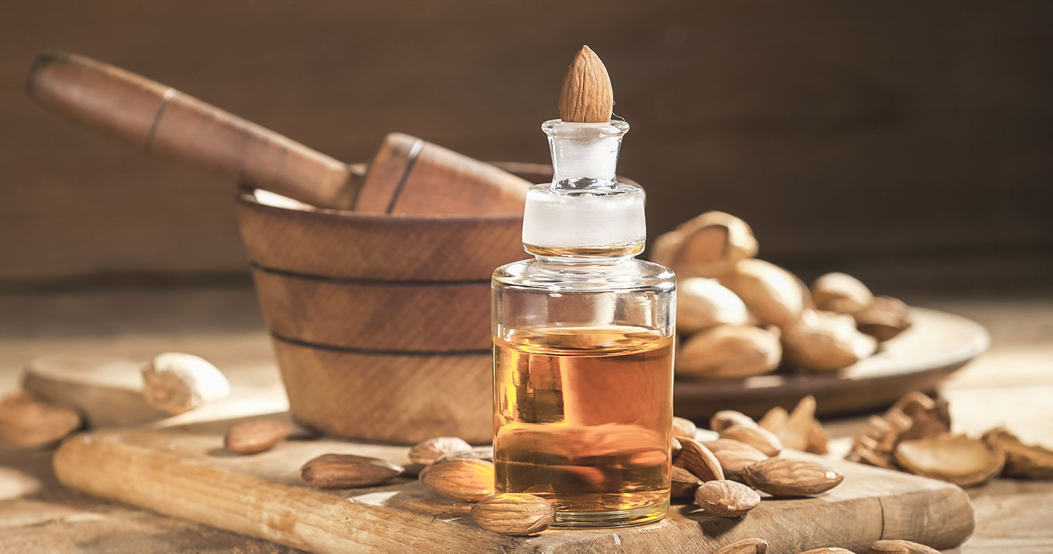 A bottle of Almond oil with a piece of Almond at the cap of the bottle