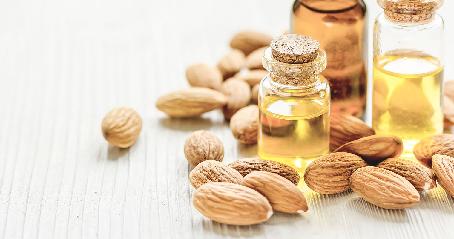 Small bottles of Almond oil surrounded by Almond seeds