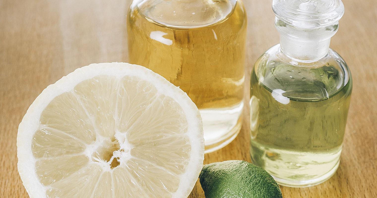Cut open Lemon with bottle of Lemon juice and Lemon essential oil