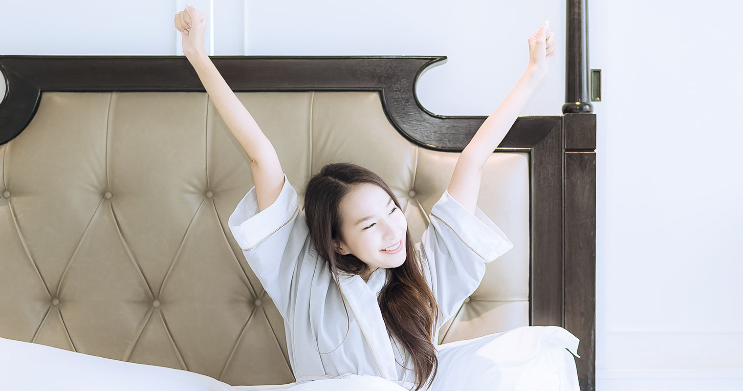 girl wake up in bed in the morning feeling refreshed