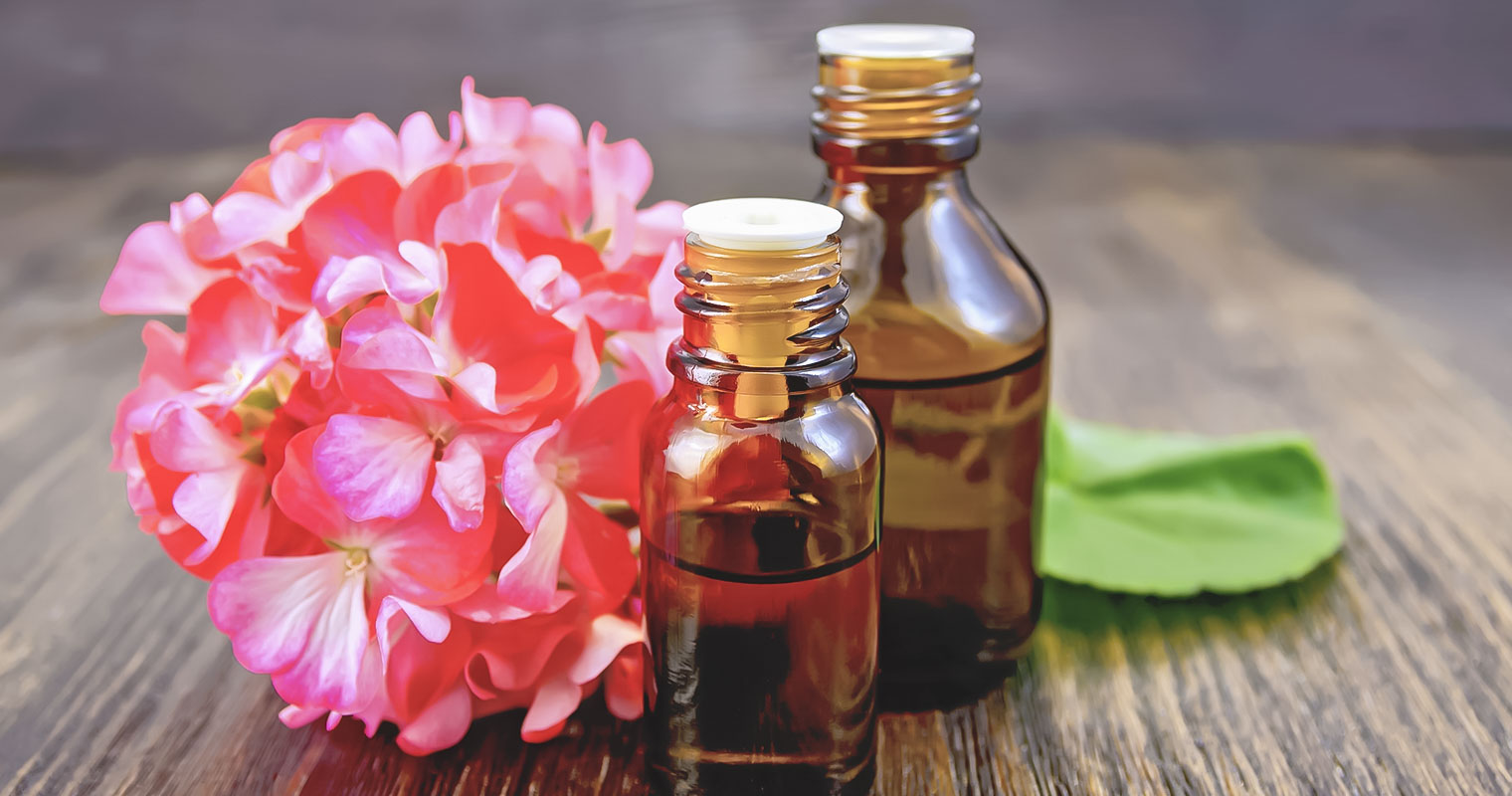 2 bottles of Geranium oil in front of Geranium flower on a table