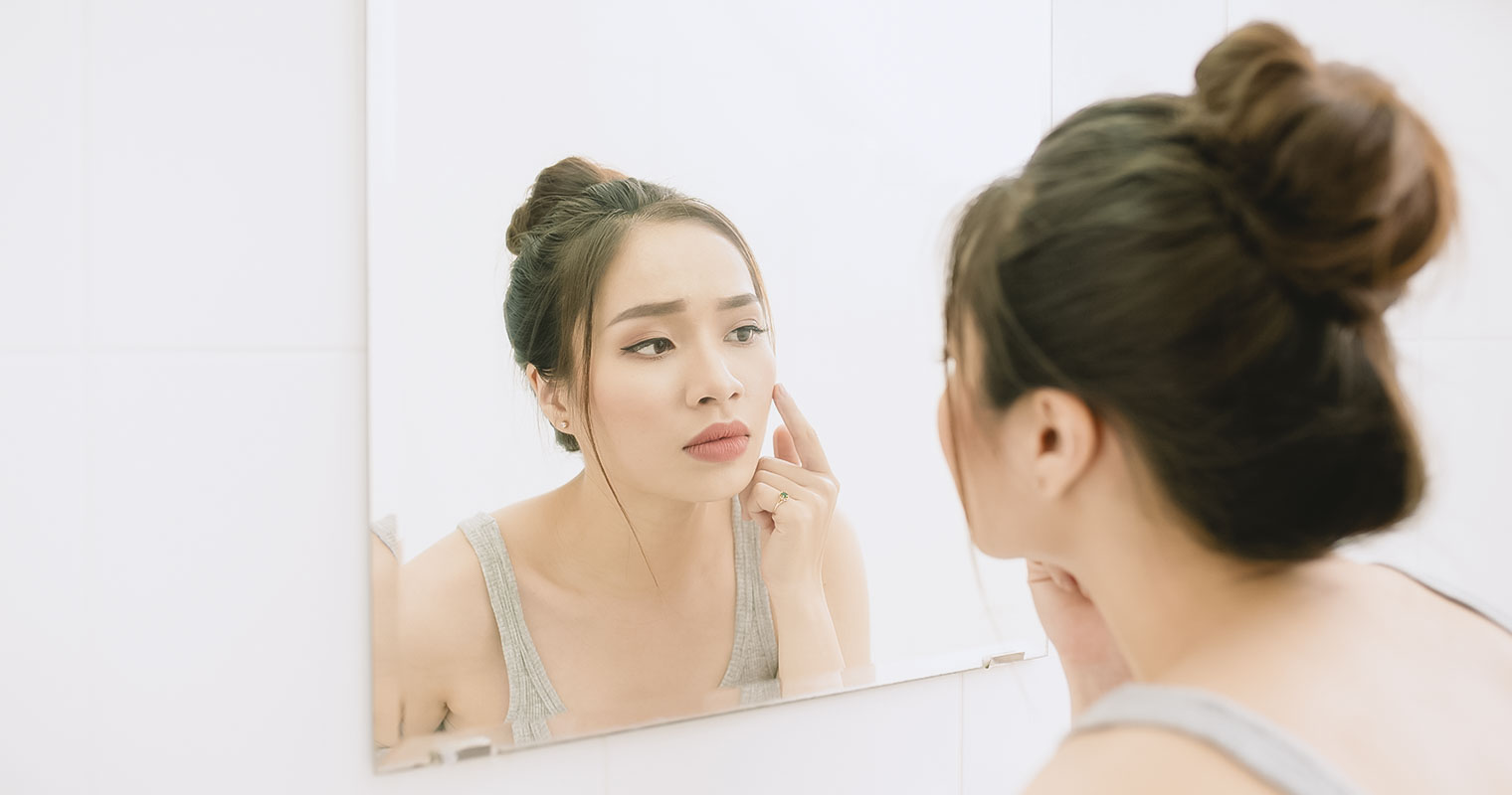 Girl looking at her breakout in front of mirror